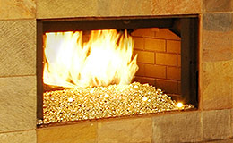 Gold Reflective Nugget Diamond Fire Glass installed in an outdoor fireplace